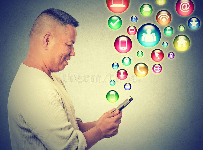 Gelukkige mens die het texting op smartphone sociale media toepassingspictogrammen gebruiken die omhoog vliegen stock afbeeldingen