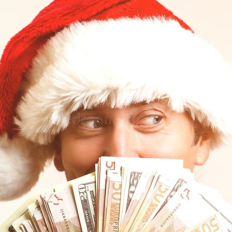 Gelukkige mens die Kerstmishoed status geïsoleerd over witte muur dragen Opzij het kijken Kerstman die geld houden Kerstmisverkoo royalty-vrije stock foto