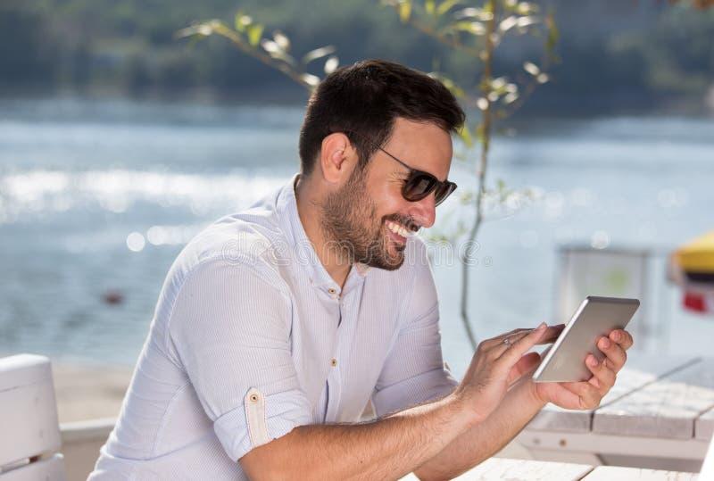 Gelukkige mens die met tablet op strand genieten van stock afbeeldingen
