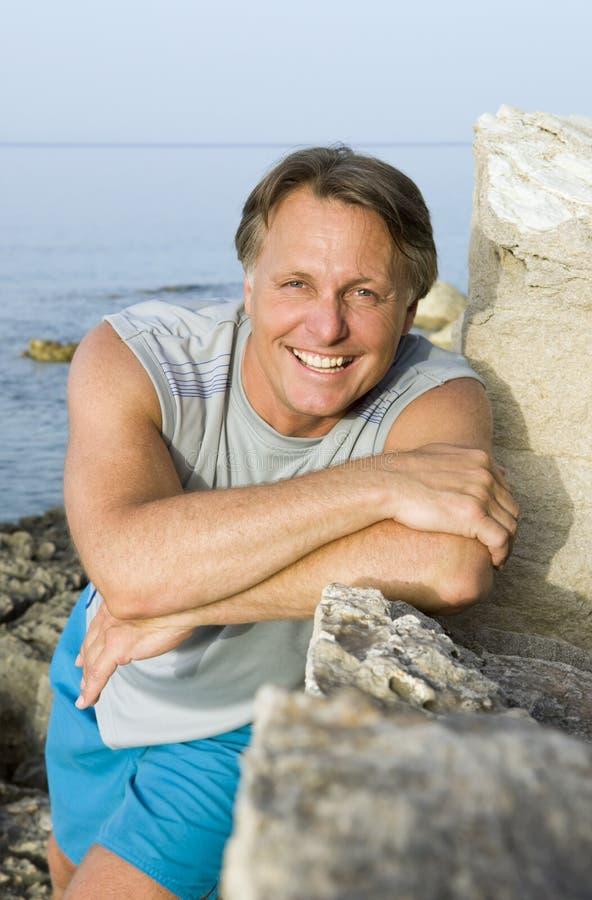 Gelukkige mens die op een rots leunt royalty-vrije stock fotografie