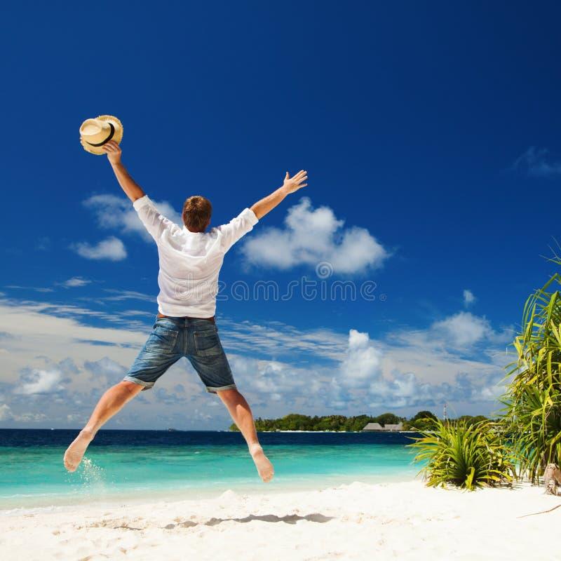 Gelukkige mens die op het tropische strand springen stock foto's