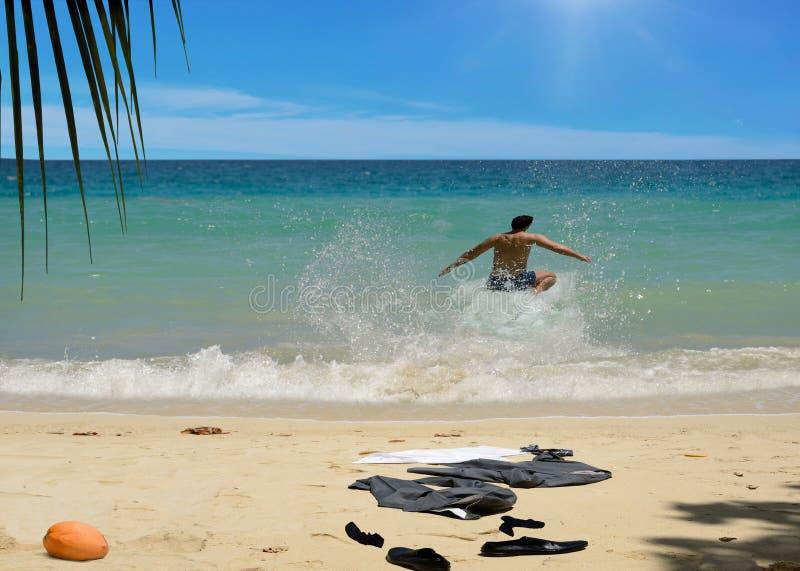 Gelukkige mens die in overzeese golven springen Pak op strand stock afbeelding