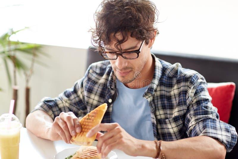 Gelukkige mens die sandwich eten bij koffie voor lunch stock foto