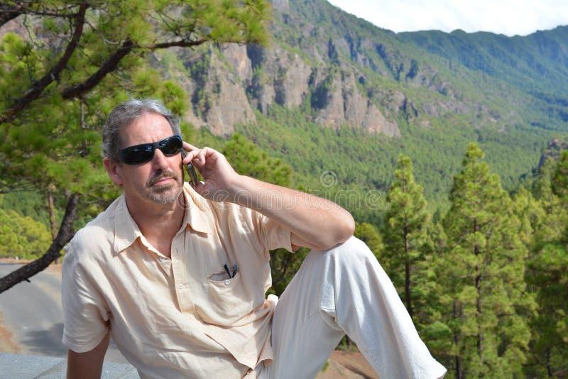 Gelukkige mens die telefonisch op de bank in het park spreken royalty-vrije stock afbeelding