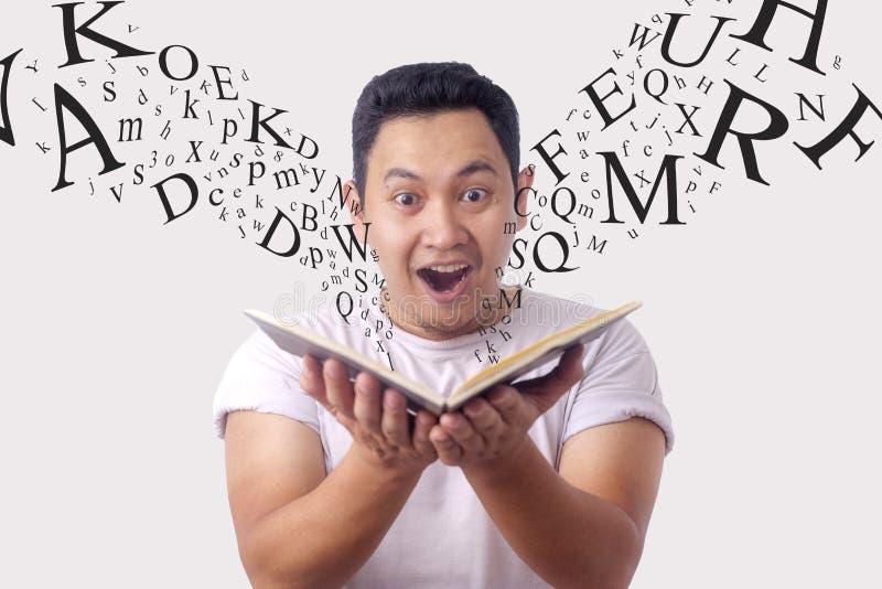 Gelukkige Mens die terwijl het Lezen van Boek glimlachen stock foto's