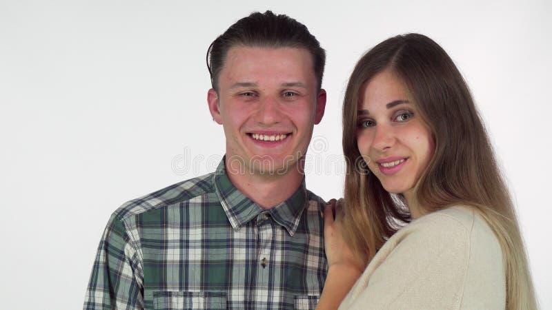 Gelukkige mens die wanneer zijn mooi meisje die hem kussen op de wang glimlachen stock afbeelding