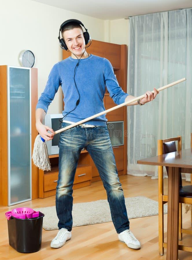 Gelukkige mens die zijn huis met zwabber schoonmaken stock afbeelding