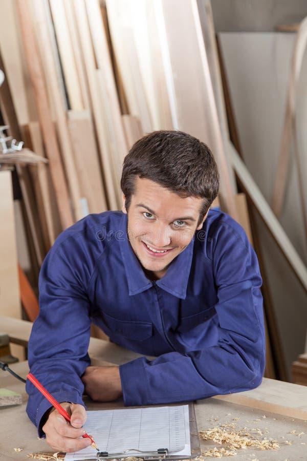 Gelukkige mens die in zijn workshop schrijven royalty-vrije stock afbeelding