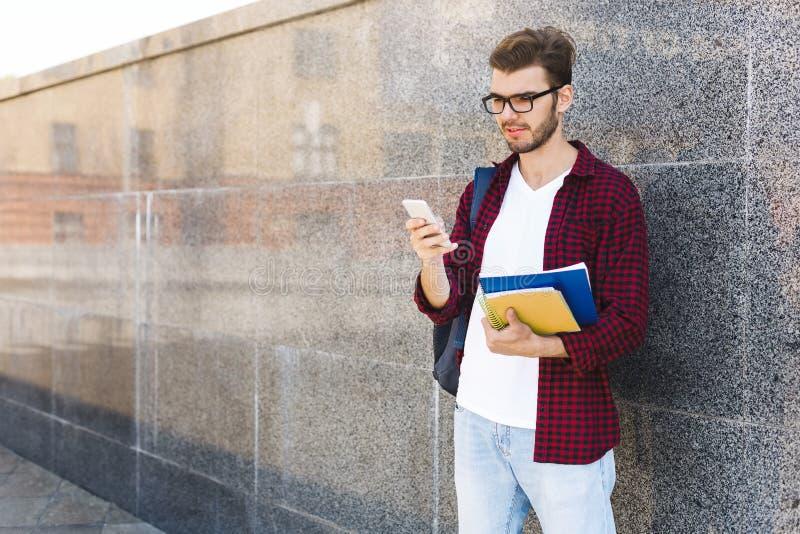 Gelukkige mens in glazen die op grijze achtergrond in openlucht texting royalty-vrije stock fotografie