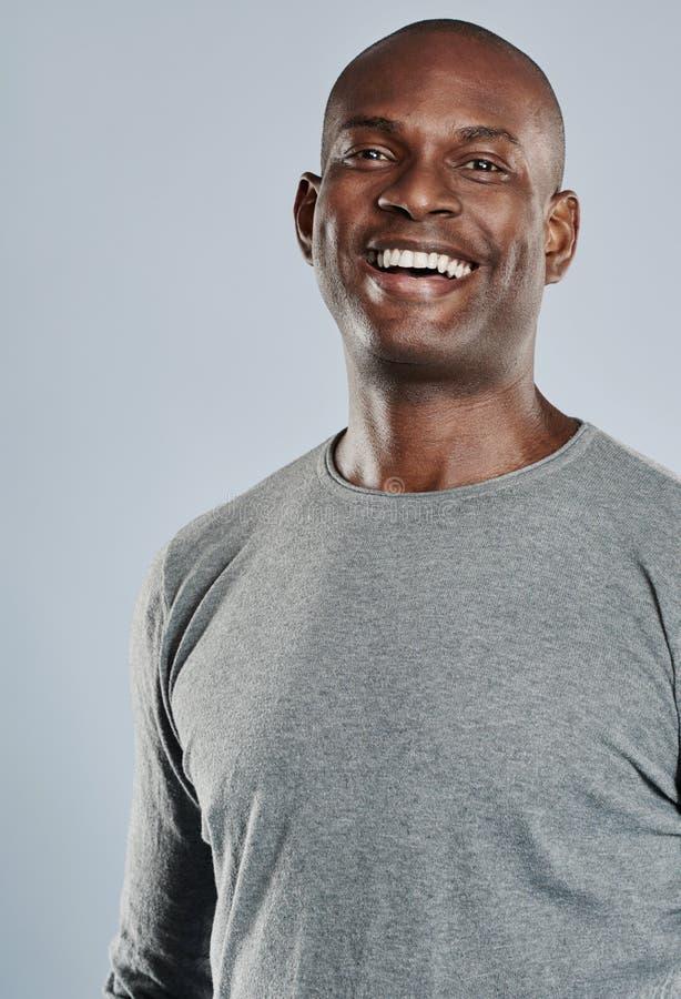 Gelukkige mens in het grijze overhemd lachen stock foto
