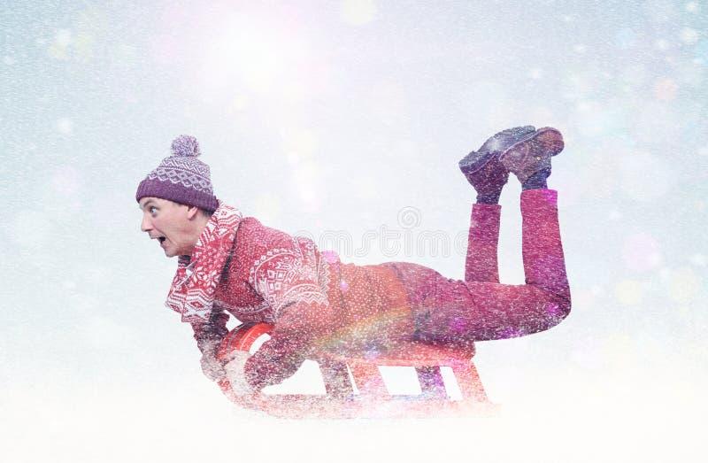 Gelukkige mens in het rode sweater sledding De winter, zon, sneeuw, gloed royalty-vrije stock afbeeldingen