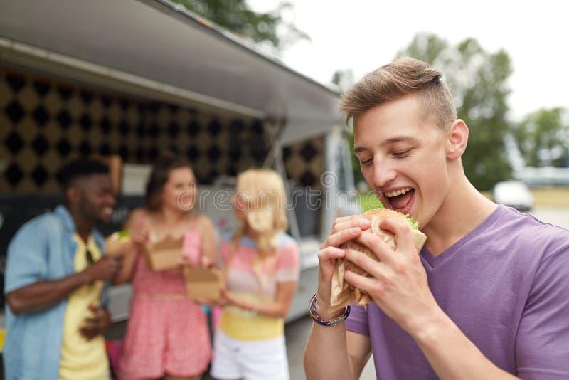 Gelukkige mens met hamburger en vrienden bij voedselvrachtwagen royalty-vrije stock foto's