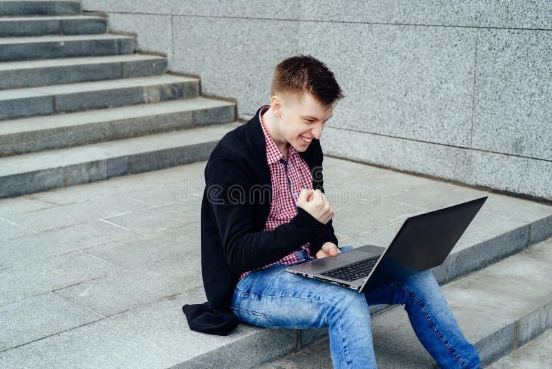 Gelukkige mens met laptop computer Ik deed het! Knappe jonge mensenloo stock afbeeldingen