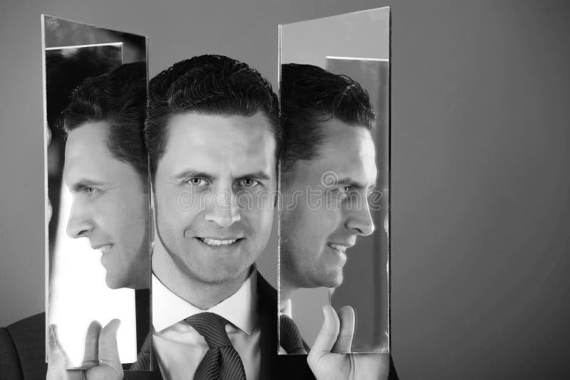 Gelukkige mens met volledige gezicht en profielen tussen twee spiegels stock foto