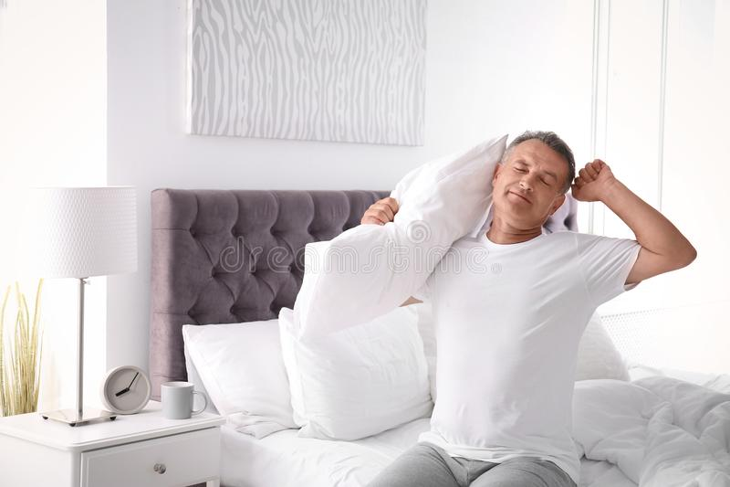 Gelukkige mens met zachte hoofdkussenzitting op bed royalty-vrije stock afbeeldingen