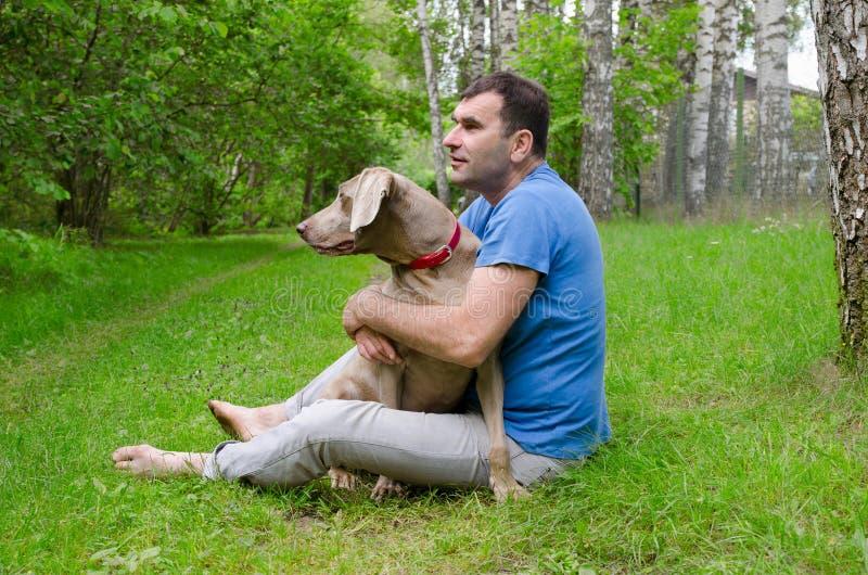 Gelukkige mens met zijn hond stock afbeelding