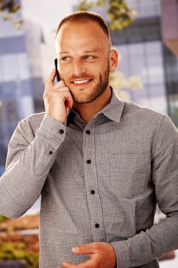 Gelukkige mens op mobilofoon stock afbeelding