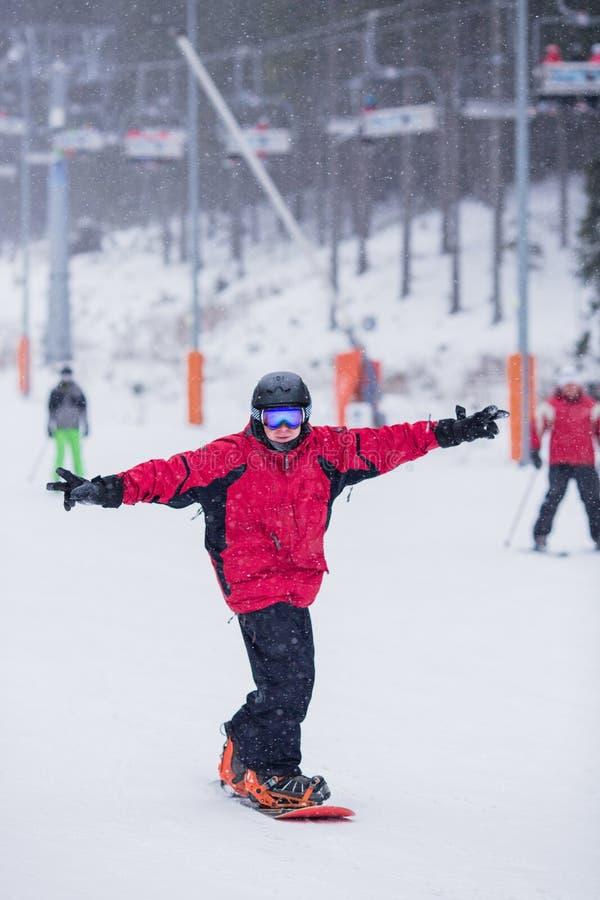 Gelukkige mens in rood jasje op snowboard skiin neer op berg Het sneeuwt stock foto's