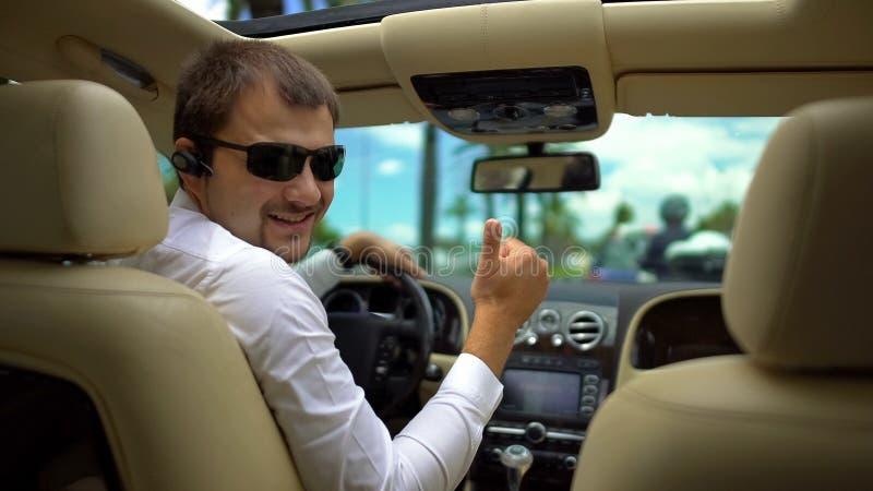 Gelukkige mens in zonnebril die auto op vakantie drijven, die duim-op handgebaar tonen stock foto's