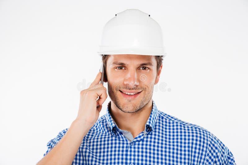 Gelukkige mensen bouwingenieur in helm die op mobiele telefoon spreken royalty-vrije stock afbeelding