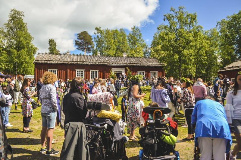 Gelukkige mensen die en op de Zweedse medio viering van de de zomerdag met kleurrijke kleding en blauwe hemel in genieten van wac royalty-vrije stock fotografie