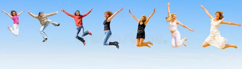 Gelukkige mensen die met vreugde springen stock foto