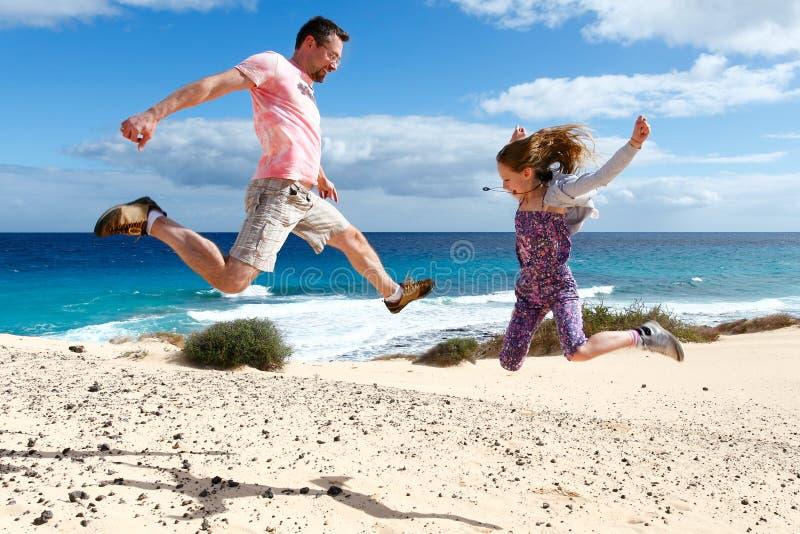 Gelukkige mensen die op een strand springen royalty-vrije stock afbeelding