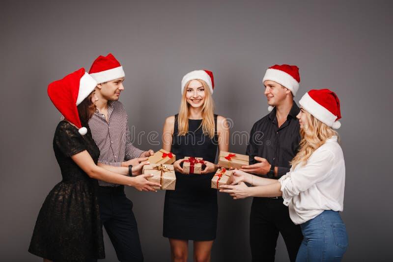 Gelukkige mensen in Kerstmankappen met giftdozen stock afbeelding
