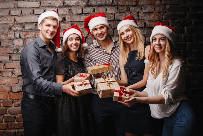 Gelukkige mensen in Kerstmankappen met giftdozen stock afbeeldingen