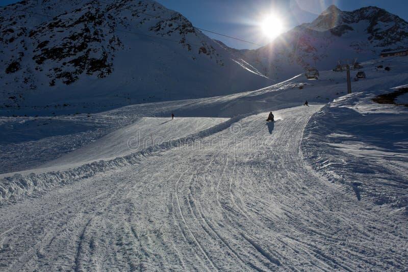 Gelukkige mensen, kinderen en volwassenen, die op een zonnige dag in de bergen van Tirol glijden stock fotografie