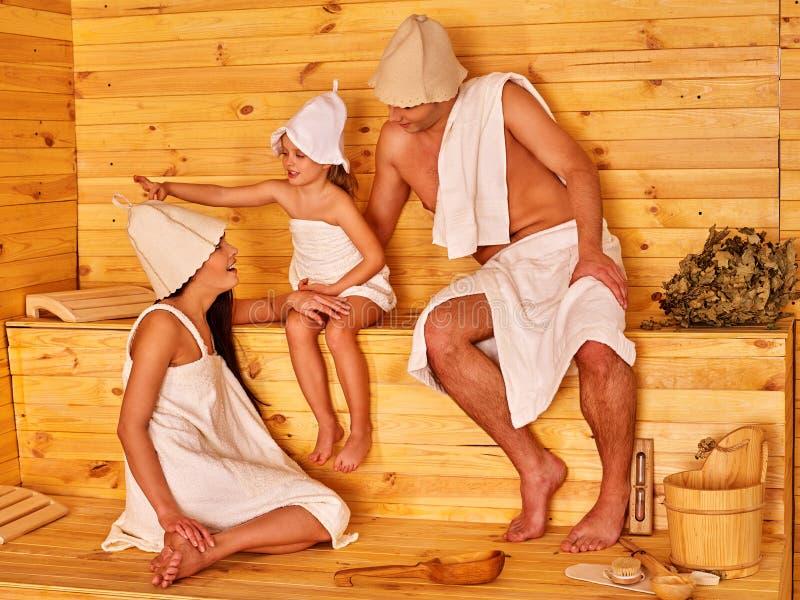 Gelukkige mensen met kind in hoed bij sauna stock foto's