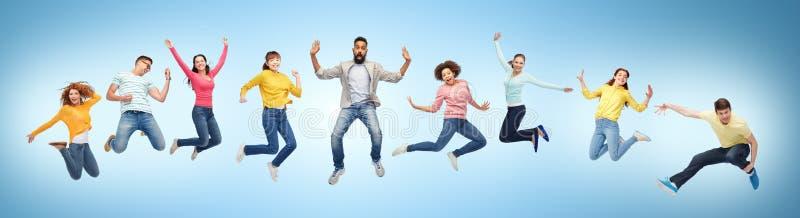 Gelukkige mensen of vrienden die in lucht over blauw springen royalty-vrije stock foto