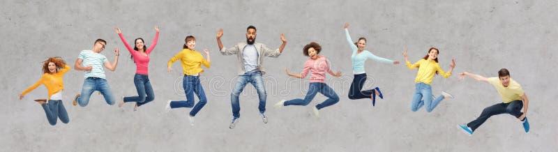 Gelukkige mensen of vrienden die in lucht over grijs springen stock fotografie