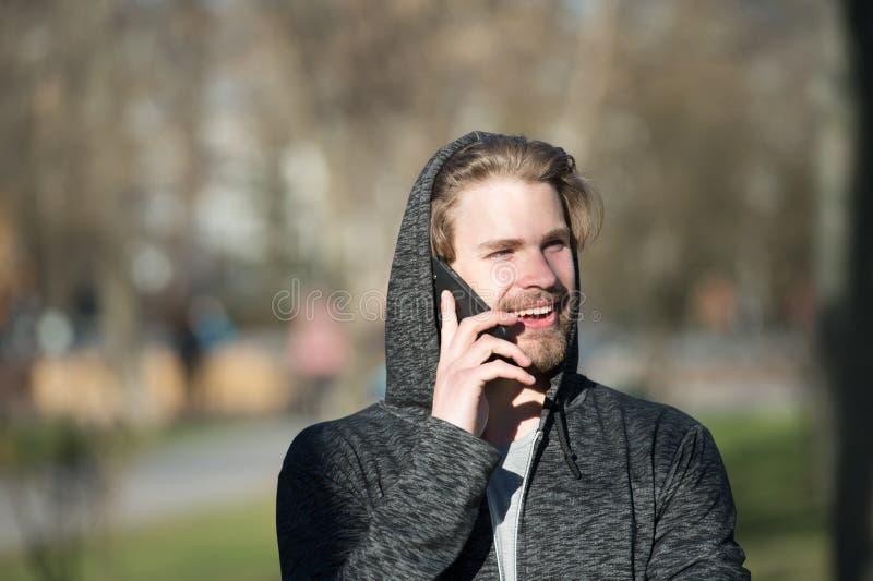 Gelukkige mensenbespreking op mobiele telefoon in park, mededeling stock foto's