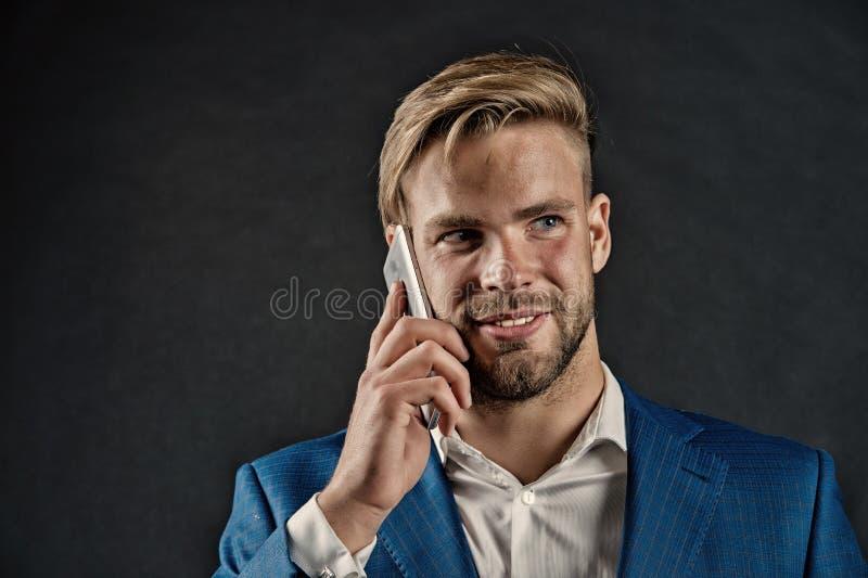 Gelukkige mensenbespreking op smartphone Zakenmanglimlach met mobiele telefoon Bedrijfslevensstijlconcept Bedrijfs mededeling royalty-vrije stock foto's