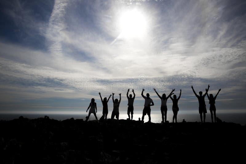 Gelukkige mensensilhouetten op het strand stock foto's