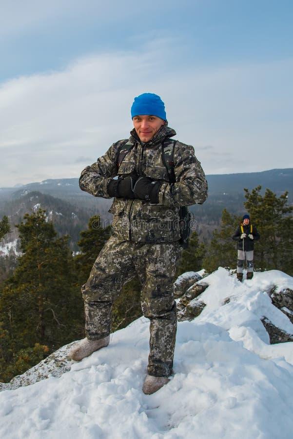 Gelukkige mensenwandelaar die zich bij bergbovenkant bevinden in de winterdag royalty-vrije stock foto
