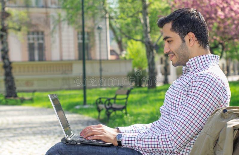Gelukkige mensenzitting op bank en het gebruiken van laptop stock foto