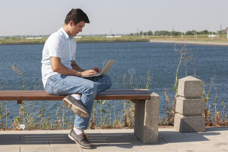 Gelukkige mensenzitting op bank en het gebruiken van laptop in een park stock fotografie