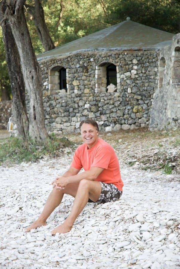 Gelukkige mensenzitting op strand royalty-vrije stock afbeelding
