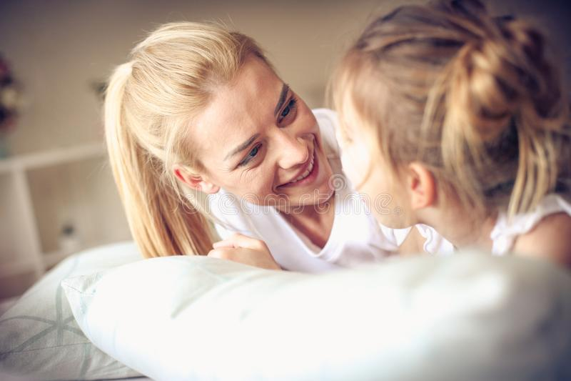 Gelukkige middenleeftijdsmoeder met haar dochter die op een bed liggen royalty-vrije stock foto