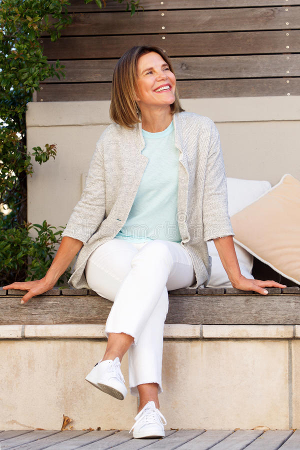 Gelukkige middenleeftijdsvrouw die buiten ontspannen stock afbeelding