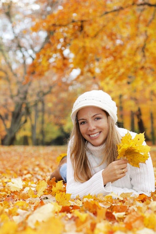 Gelukkige middenleeftijdsvrouw die op de grond met de herfstbladeren liggen royalty-vrije stock foto