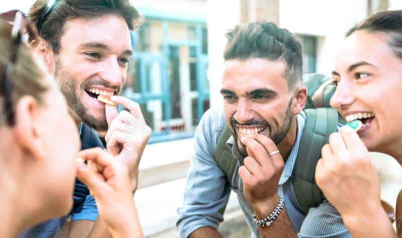 Gelukkige millenial vrienden die pret hebben op stadscentrum die suikersuikergoed eten - z-het concept van de generatievriendscha royalty-vrije stock fotografie
