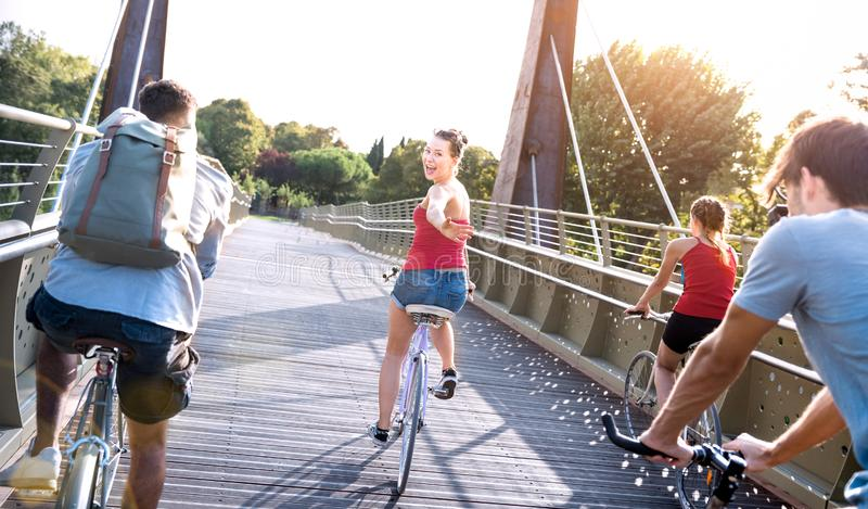 Gelukkige millennial vrienden hebbend pret berijdende fiets bij stadspark - Vriendschapsconcept met het jonge millenial mensenstu stock foto