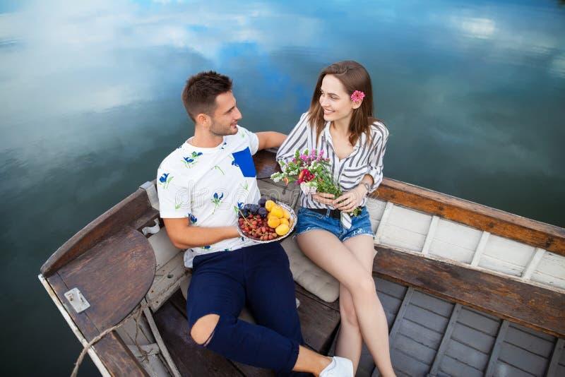 Gelukkige minnaars die in boot op een meer ontspannen stock fotografie