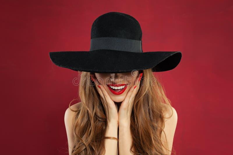 Gelukkige modelvrouw met rode lippenmake-up en manicure op rode achtergrond Mooi verrast model in zwart hoedenportret stock fotografie