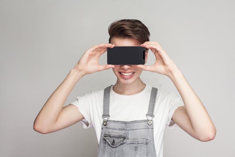 Gelukkige moderne jonge jongen in deminoverall en witte T-shirttribune royalty-vrije stock foto's