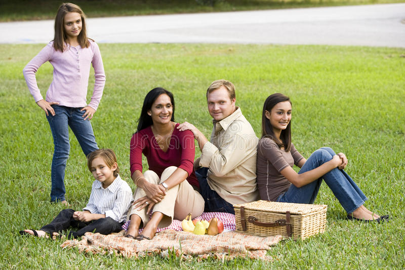 Gelukkige moderne multiculturele familie die van picknick geniet stock afbeelding