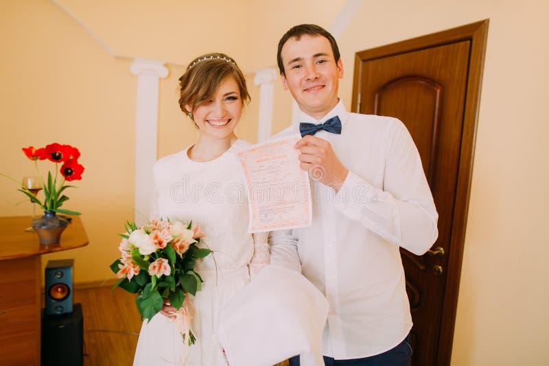 Gelukkige modieuze blondebruid en de knappe huwelijksakte van de bruidegomholding stock foto